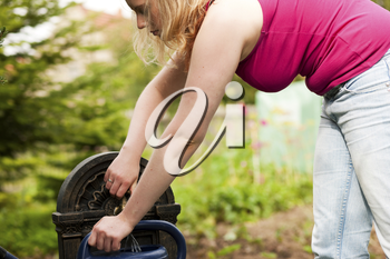 Garden scene - woman refilling the watering pot at a tap