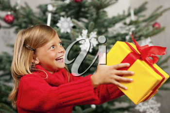 Young girl in front of the Christmas tree showing the world the present she received
