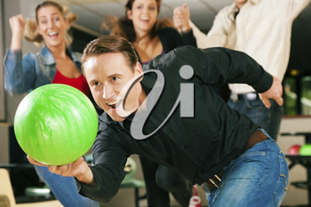 Group of four friends in a bowling alley having fun, three of them cheering the one in charge to throw the ball