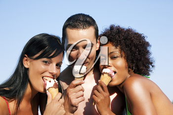 Group of friends - one man and two women eating ice cream in swimwear and bikini, it seems to be a hot summer day