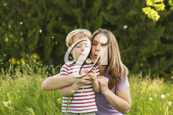 Little boy and his mother blowing dandelion seed for a wish on a meadow outdoors in summer