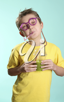 Boy enjoying a healthy juice. Green health juice containing wheatgrass, barley grass and sprirulina.  A great way to cleanse and detoxify the internal organs.