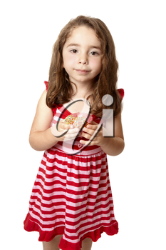 Young child holding a pink iced doughnet.   She is wearing a pink and red striped dress with little pink  heart buttons.