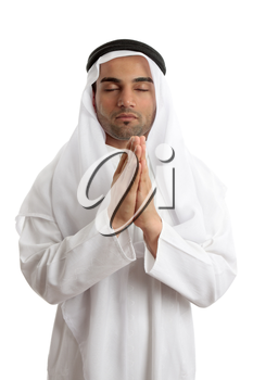 Man wearing middle easter attire with hands together in quiet prayer.