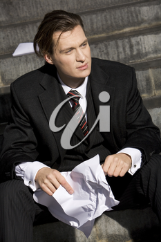 Portrait of handsome business leader with crumpled piece of paper in hands
