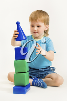 Photo of young boy making tower from toy brick