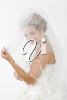 Portrait of happy bride looking at camera with smile through her veil