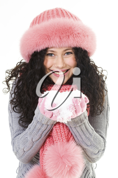 Portrait of cheerful woman in pink winter fur cap holding snow in hands