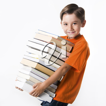Portrait of handsome pupil with huge pile of books looking at camera