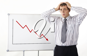 Portrait of frustrated man touching his head with whiteboard representing decreasing graph on it