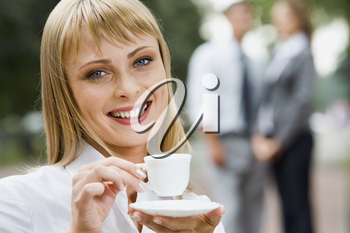 Beautiful young smiling woman with the cup of coffee outdoor