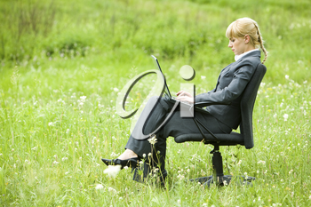 Photo of serious businesswoman sitting on armchair outside and typing on laptop