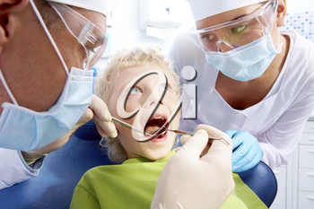 Image of little boy having teeth checked by doctor and assistant