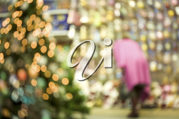 Image of blurred new year fir tree in mall with woman wearing pink coat at background