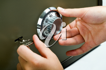 A business man opens his metal safe