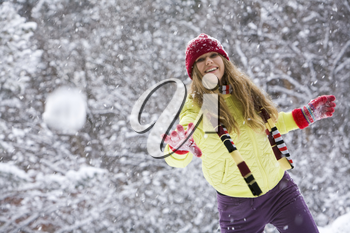 Moment of play: young woman flinging the snowball