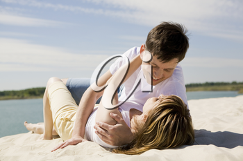 Image of amorous couple lying on sandy beach and embracing at each other