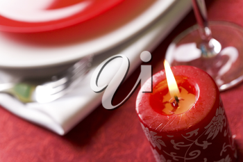 Close-up of red burning candle on festive table