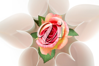 View from above of floral form made up of paper hearts with rose in its centre
