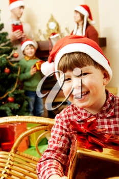 Portrait of joyful little boy holding present on the background of his relatives