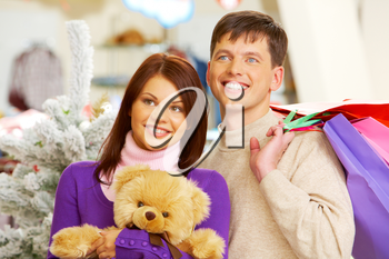 Photo of smiling woman with toy in hands and man holding paperbags in the mall