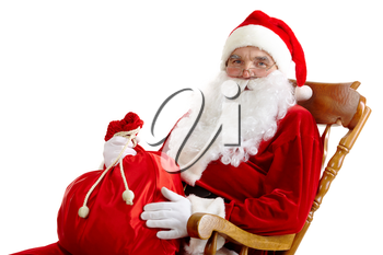 Santa sitting in the armchair and holding a sack isolated on white