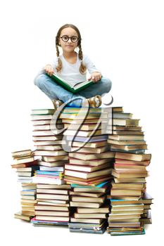 Portrait of cute girl sitting on pile of books and looking at camera