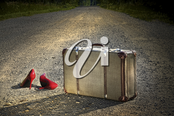 Royalty Free Photo of an Old Suitcase and Red Heels Left on a Dirt Road