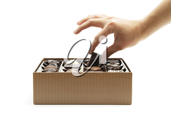 A woman's hand choosing a chocolate from a box
