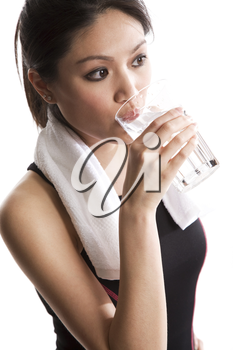 An isolated shot of a beautiful asian woman drinking water after exercising