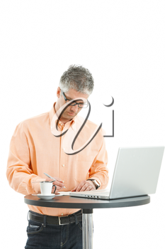 Casual businessman wearing orange shirt and jeans, standing at coffee table, using laptop computer, writing notes. Isolated on white.