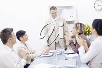Group of businesspeople sitting at table in meeting room, clapping and looking at smiling businessman.