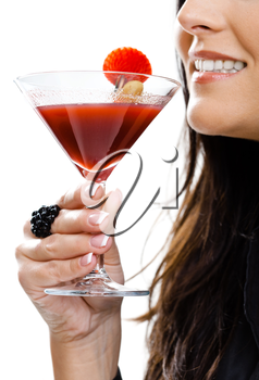 Partially visible young woman holding glass of cocktail. Selective focus on hand.
