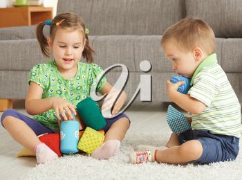 3-4 years old children playing together on the floor at home