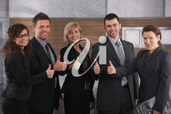 Portrait of happy businesspeople standing in office showing OK sign, smiling.
