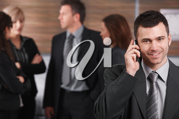 Portrait of young businessman talking on mobile phone, smiling, business people in background.