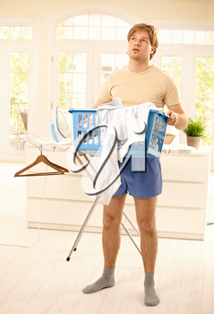 Tired young guy standing at home fed up with housework, looking up, holding washing basket.