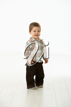 Full size portrait of cute little boy (2-3 years) in casual clothes looking at camera, smiling. Studio shot over white background.