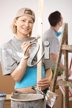 Portrait of smiling woman painting, working on new house, boyfriend standing in background.