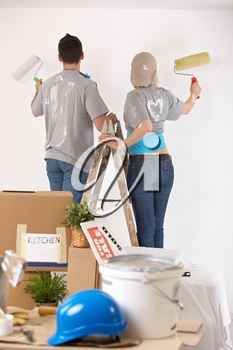 Couple standing on one ladder, painting wall together with paint roller.