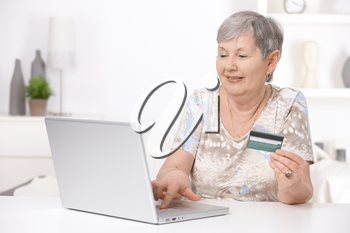 Senior woman shopping on internet, paying with credit card.