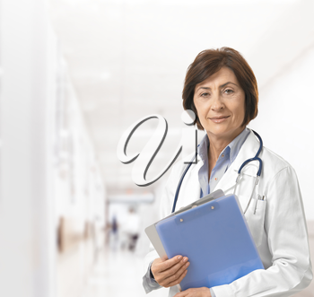 Portrait of senior female doctor on hospital corridor holding clipboard looking at camera smiling.
