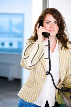 Young female receptionist receiving phone calls at office reception, smiling.