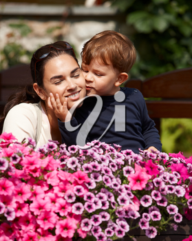 Three years old kid kissing happy mother outdoor in spring garden, smiling.