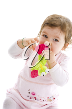 Happy baby girl sitting on floor playing with soft toy, smiling, isolated on white background.