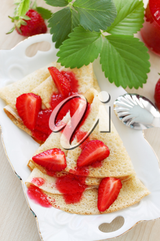 Fried pancakes with fresh strawberries and jam