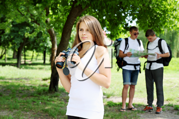 A group of young backpackers with map and binoculars