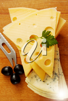 a large piece of  Swiss cheese and black olives