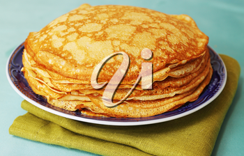 pile of ruddy pancakes on blue plate