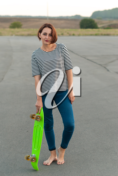 Girl standing barefoot on the asphalt with a skateboard.